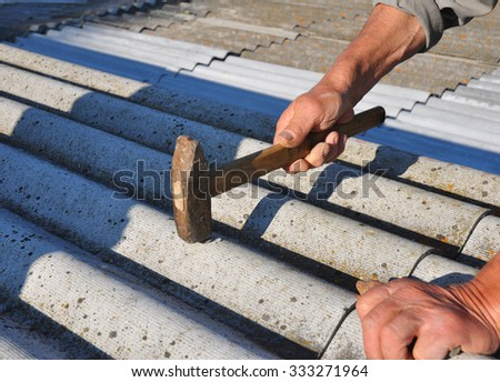 Roofer hammering nail in asbestos old roof tiles. Roofing construction - stock photo