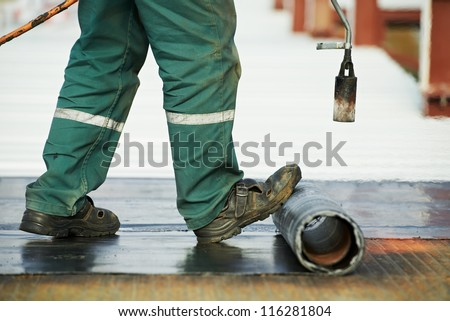 Roofer installing Roofing felt with heating and melting of bitumen roll by torch on flame during roof repair - stock photo