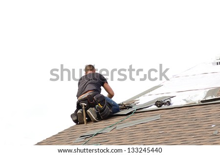 Roofer laying down asphalt roof shingles at a large commercial housing development in Oregon - stock photo