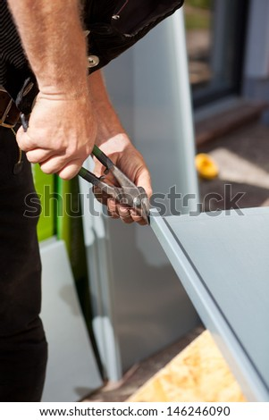 Roofer making cuts on a metal sheet using cutting pliers - stock photo