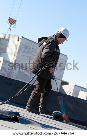 Roofer man worker at building site installing roll of roofing felt with gas blowpipe torch during construction works - stock photo