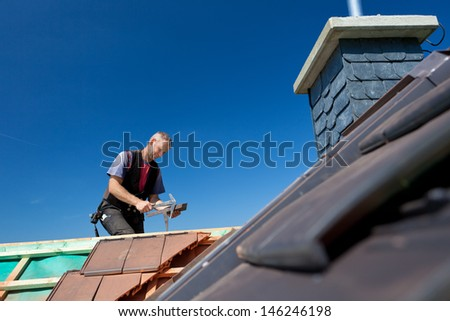 Roofer molding tiles with a slate hammer on top of the roof