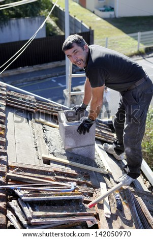 Roofer replacing shingles - stock photo