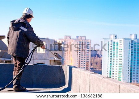Roofer worker installing roofing felt by means of gas blowpipe torch - stock photo