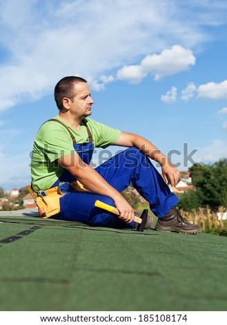 Roofer worker resting on top of building - sitting on bitumen roof shingles - stock photo