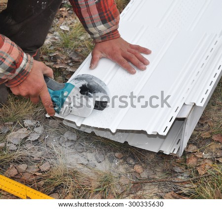 Roofer worker uses a electric tool with grinding wheel to cut soffit to roofing house.