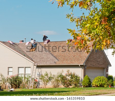 Roofers repairing the roof of a house in the suburbs. - stock photo