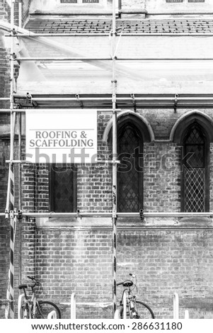Roofing and Scaffolding sign for repairs of an old building monochrome image - stock photo
