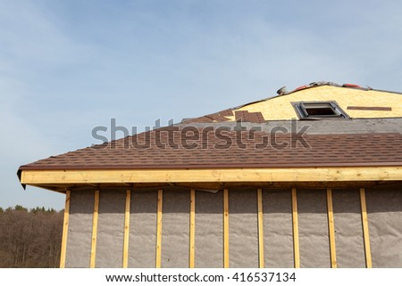 Roofing Construction and Building New Brick House with  Skylights, Attic, Dormers and Eaves. Repair Asphalt Shingles or Bitumen Tiles on the Rooftop Outdoor. - stock photo