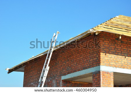 Roofing Construction. Wooden Roof Frame Unfinished House Construction with metal ladder. - stock photo