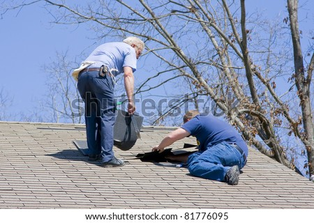 Roofing contractor repairing damaged roof on home after recent wind storms, many roofs were damaged