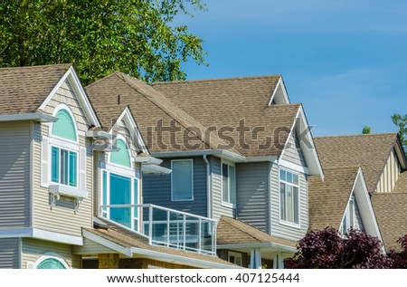 Roofs and windows of a modern houses in great neighborhood, in suburbs of Vancouver, Canada. - stock photo