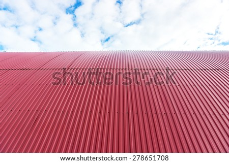 Rooftop of curved red corrugated iron on blue sky with fluffy clouds - stock photo