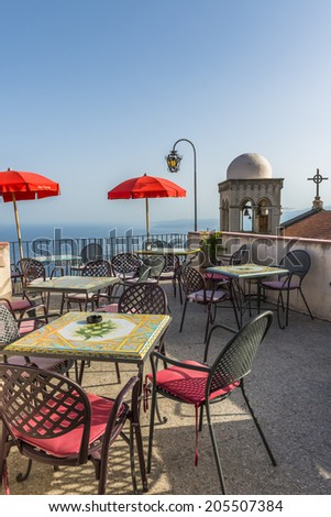Rooftop sitting area with a view of a church bell tower in in Castelmola, Sicily - stock photo