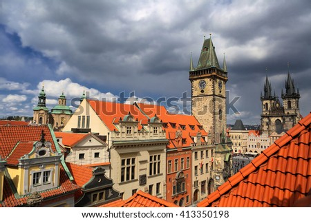 Rooftop terrace overlooking Prague Czech Republic capital city with Orloj and Church of Our Lady before Tyn on a beautiful sunny day with storm clouds - stock photo
