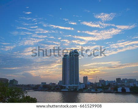 Rooftop view from a hotel looking at tall buildings on the Chao Phraya River at sunset, Bangkok, Thailand