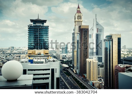 Rooftop View of famous Dubai's towers at daytime. Modern architecture of Dubai, United Arab Emirates. - stock photo
