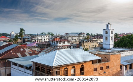 rooftop view over the african city of stonetown zanzibar showing the weathered zinc roofing and city skyline - stock photo