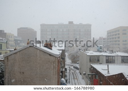 Rooftops and local alley during a seasonal snowstorm in center city Philadelphia - stock photo