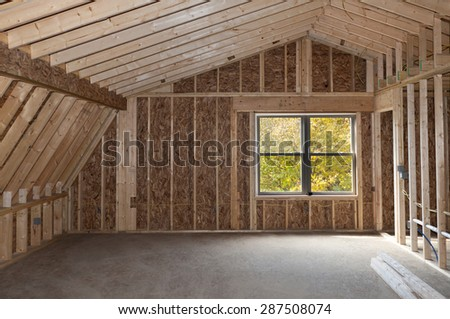 Room addition construction with pitched ceiling and autumn trees view window - stock photo