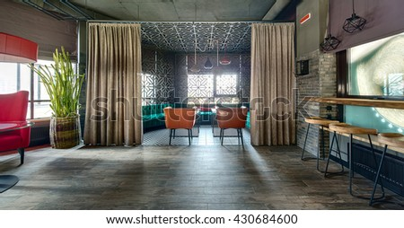 Room in a loft style in a mexican restaurant. On the left there is a crimson armchair with a glass table near it and a red lampshade over it. Big cactus in a wicker pot is behind the armchair. On the - stock photo