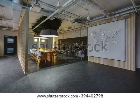 Room in a loft style. There are light and dark tables, light and dark chairs. There is stand for office supplies between light tables. Above them hang large lamps with artificial leaves. A few laptops - stock photo