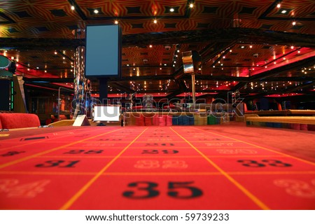 room in casino with red table for roulette game, view from table - stock photo