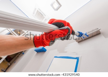 Room Interior Painting by Telescoping Roller Painter. - stock photo