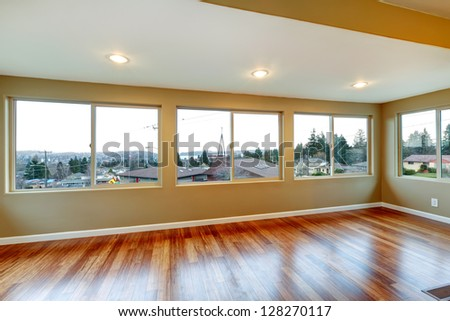 Room interior with many windows and hardwood floor.