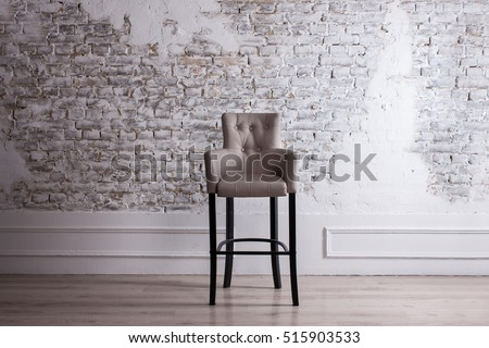 ROOM minimalism, chair in the room, the background STONE WALL, MODERN ROOM. DECORATIVE BRICK WALL WHITE AND BLACK CHAIR CHAIR. Modern living room, light background. Living room, brick wall, NEW ROOM.