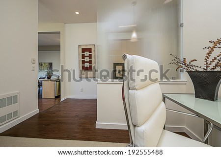 Room of start up blogger in Bay area. Home office in designer home with metal glass desk, white designer chair and flowers. - stock photo