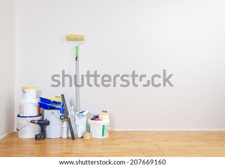 Room repairs. Cans with paints, roller, screwdriver. - stock photo