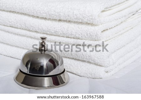Room service bell and towels - stock photo
