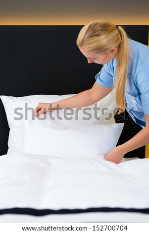 Room service - young chambermaid changing the bedding or bedclothes in a hotel room - stock photo