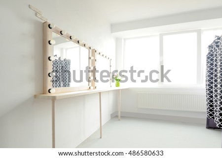 Room with makeup mirror lights and window