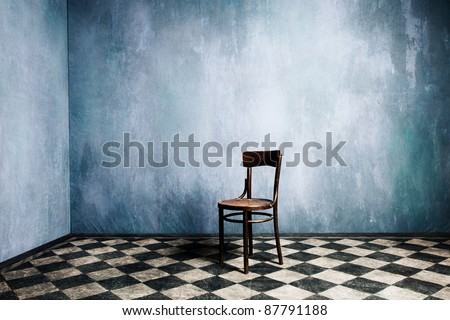 room with old blue walls and tiled floor with wooden chair in the middle - stock photo