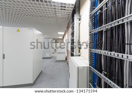 Room with rows of racks with equipment for telecom and cables. - stock photo