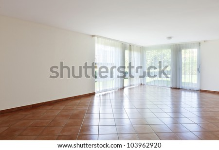 room with terracotta floor,windows with white curtains