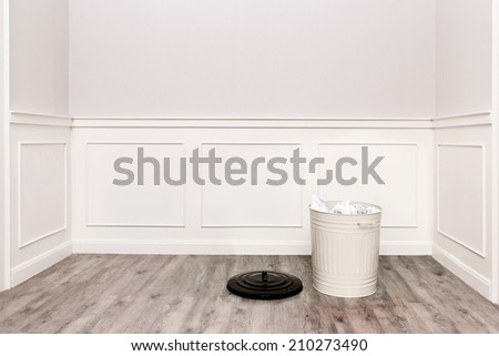 room with trash bin filled with papers on wooden floor - stock photo