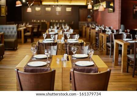 Roomy hall in restaurant with wooden furniture and walls of red bricks - stock photo