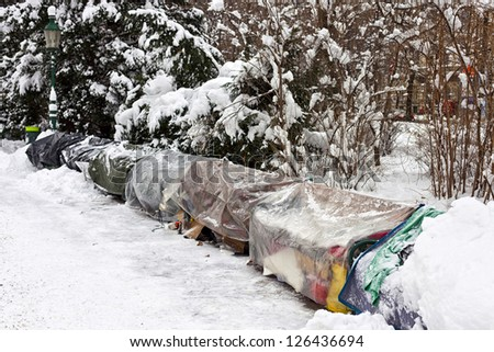 Roost of some homeless people on the bench of a public park. - stock photo
