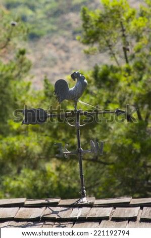 rooster weather vane attached to roof