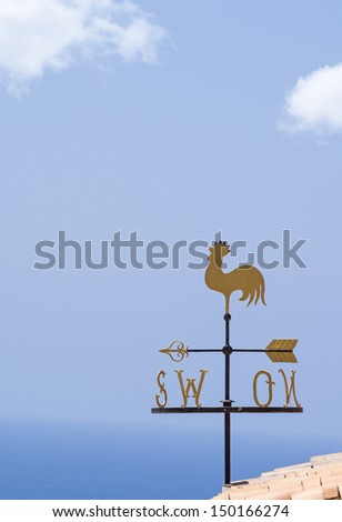 Rooster wind cock weather vane on a tiled roof against clear blue sky - stock photo