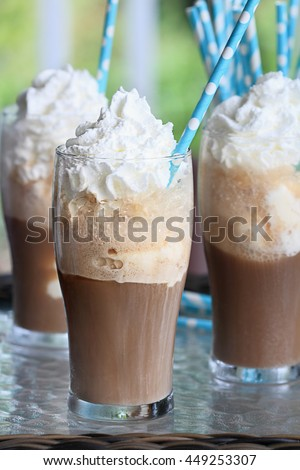 Root beer floats with whipped cream and colorful party straws. Extreme shallow depth of field with focus on center glass.