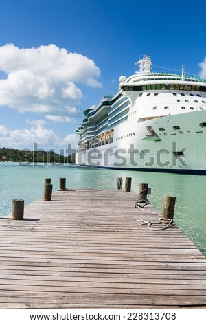 Rope coiled on an old wooden pier with a white luxury cruise ship in the background - stock photo