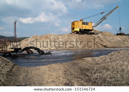 Rope excavator for mining sludge among piles of sand, black sludge polluted water gushing from a pipe, black stream polluted water, environmental pollution - stock photo