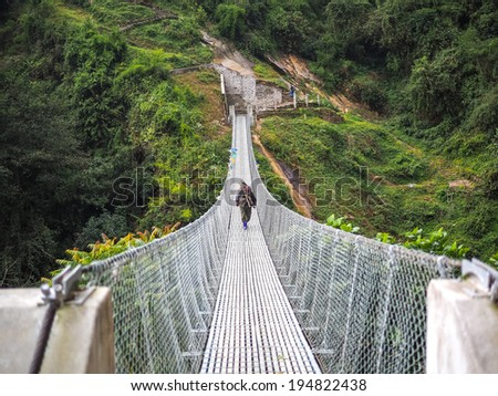 rope hanging suspension bridge in Nepal - stock photo