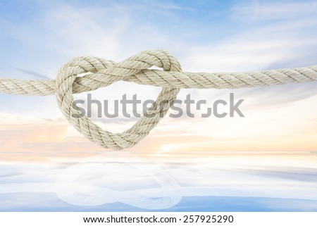 rope in shape of heart with shadow on ray of sunlight glow behind the cloud on the sky background - stock photo