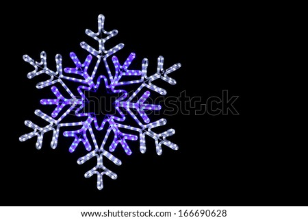 Rope-light coloured snowflake on a black background - stock photo