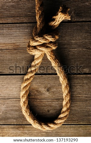 Rope noose with knot over old wooden background - stock photo